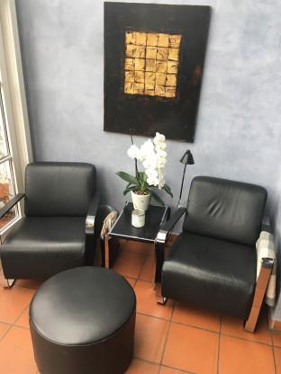 2 schwarze Leder Sessel + Leder Hocker